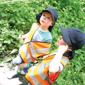2 children in shorts and hi-visibility jackets on surrounded by vibrant green plants.
