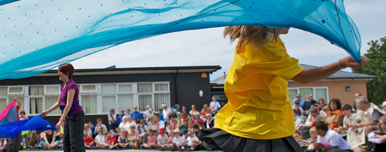 A young girl running with a ribbon on a primary school playground with teachers, parents and pupils eagerly sat watching.