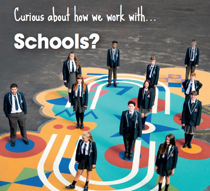 12 school children smiling at the camera and stood on a piece of flamboyant art on the playground. Text reads: Curious about how we work with...Schools?