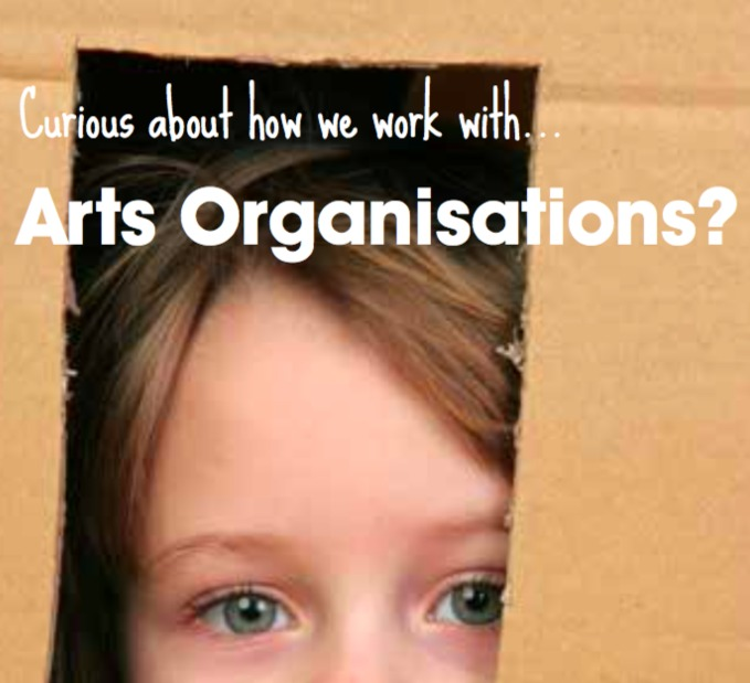 Close-up of a young child looking directly at the camera through a cut-out of a brown box. Text reads: Curious about how we work with... Arts Organisations?