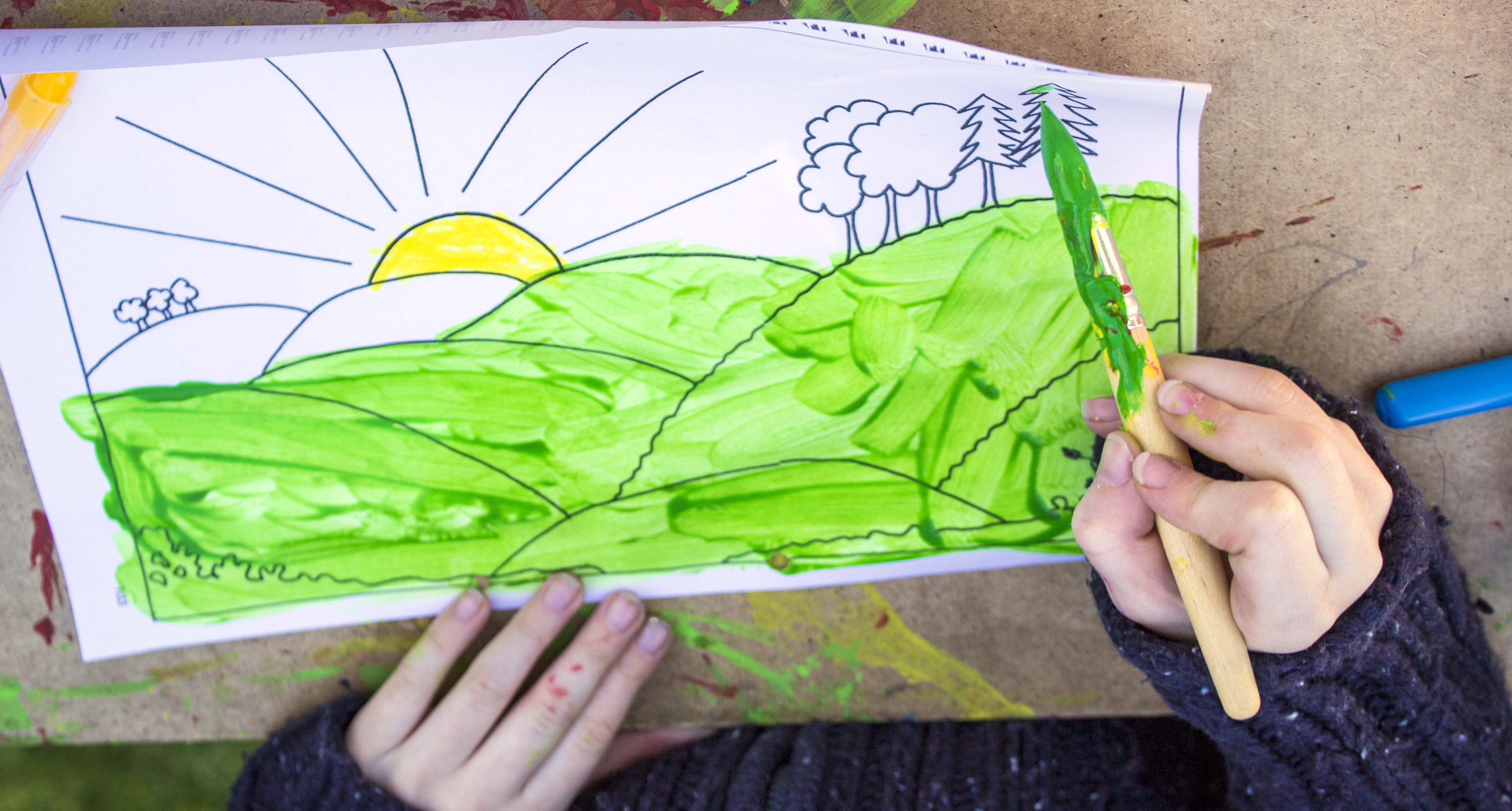 A child's hands painting a colourful picture of a sun rising over a bunch of green fields.