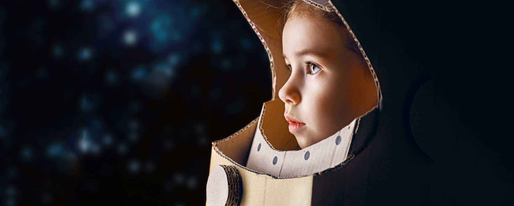 Young child in a self made astronaut helmet looking out with determined wonder at the stars.