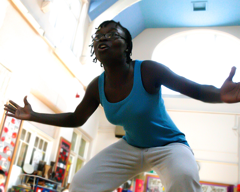 A dance practitioner in a school classroom dynamically posed.