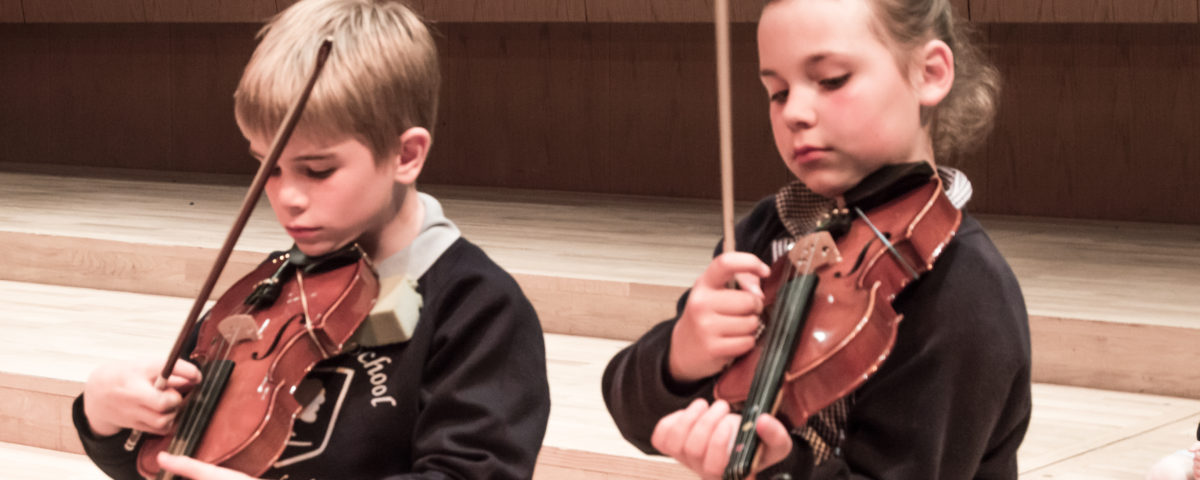 Young school boy and girl learning to play the violin with concentration.
