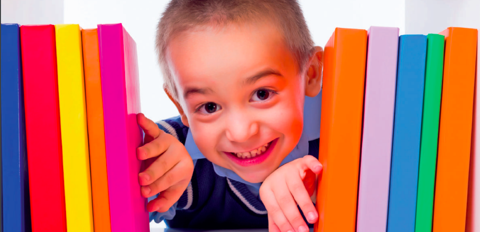 Small school child poking his through a bunch of vibrant coloured library books on a shelf.