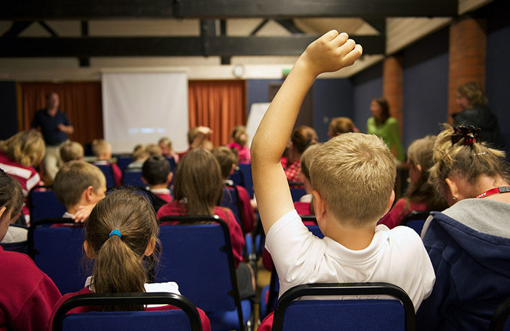 School boy in the foreground with his arm raised in a classroom full of children all sat facing an electronic white board.