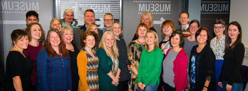 Curious Minds Team. A large group of people from a range of ages and hairstyles - predominantly women and all smiling!