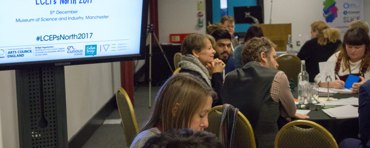 "A diverse room of people sat at tables discussing creative ideas. There is a monitor with the writing: ""LCEPs North 2017"" with the logos of several arts organisations such as Curious Minds and the Arts Council England."