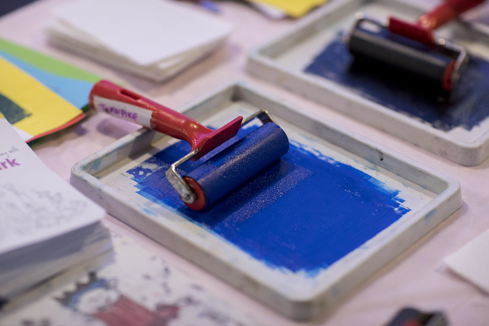 Paint roller on a table - the paint is blue and there are colours across the table.