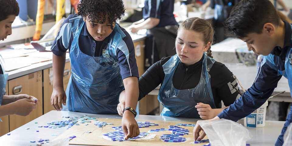 4 diverse school children doing art in a classroom.