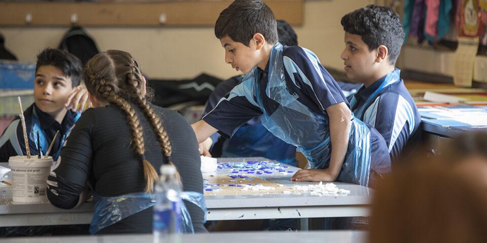 Children in an art classroom using materials.