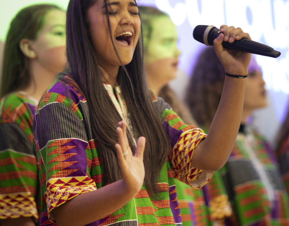 Young person holding microphone enjoys performing with other choir members